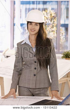Mulher inteligente, com cabelos longos, vestindo repairing sorrindo para câmera, permanente no Instituto brilhante.?
