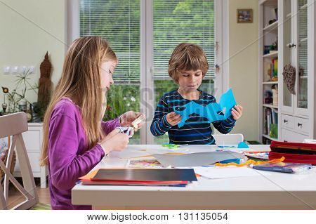 Cute boy and a girl sitting at the table drawing and cutting paper with scissors. Being creative developing imagination creativity do it yourself concept