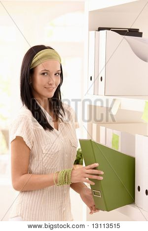 Smiling young woman busy with arranging folders on shelf, looking at camera.?