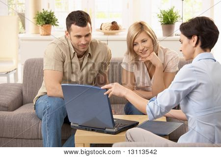 Advisor explaining on laptop, young couple listening.