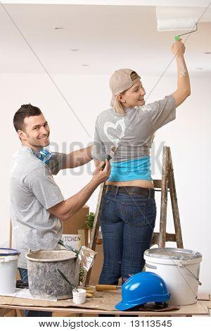 Mulher sorridente pintura em pé na escada, o teto rindo coração de pintura de cara na camiseta.