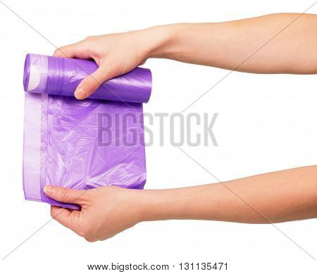 Roll lilac garbage packages in female hands isolated on white background.