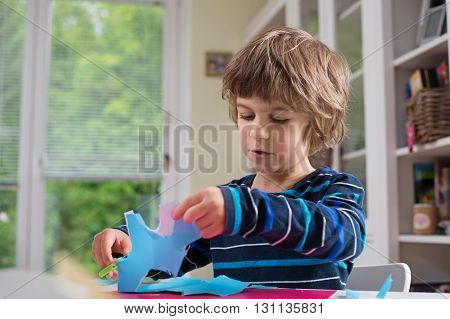 Cute litle boy cutting shapes out of colored paper. Being creative developing imagination creativity do it yourself concept