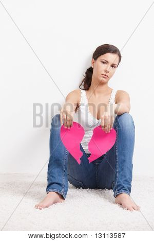Heart-broken female sitting on floor sadly, holding a torn paper heart in hands.?