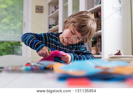 Cute little boy cutting shapes out of colored paper. Being creative developing imagination creativity do it yourself concept
