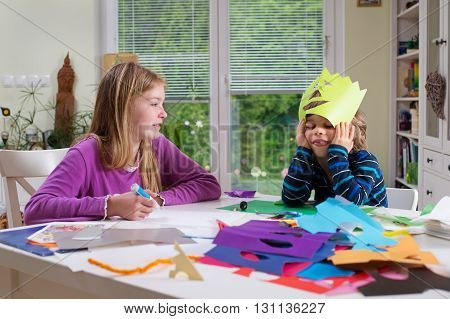 Cute little boy showing his sister or friend mask he cut out of colored paper. Do it yourself toys supporting creativity learning by doing learning through experience.