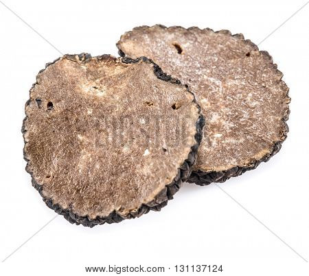 Slices of black summer truffle on a white background.