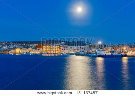 The picturesque view of the old port with the waterfront of Chania in the moonlight. Crete, Greece.
