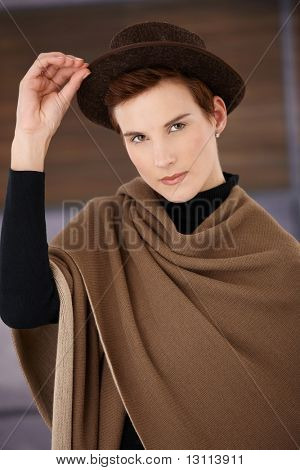 Trendy woman wearing polo-neck top and big beige scarf posing with hat, looking at camera.?