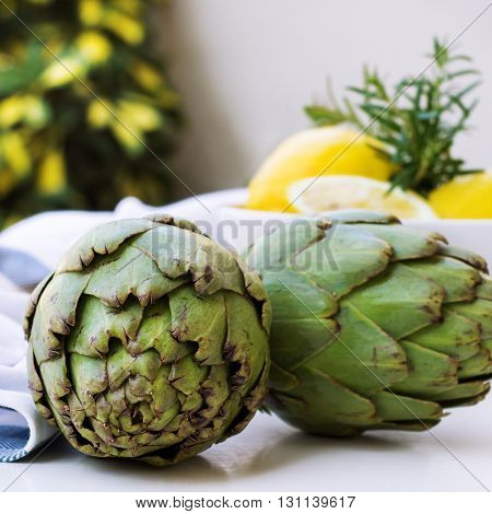 Organic fresh artichokes with lemon on a white table. Summer outdoor background. Selective focus