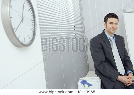 Portrait of businessman wearing grey suit and blue shirt, sitting in office, smiling.?