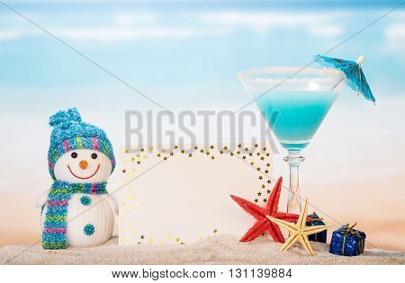Blank card, cocktail, sea star, snowman and gifts in the sand against the sea.