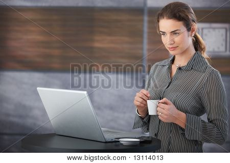 Young attractive businesswoman preparing for presentation during coffee-break.?