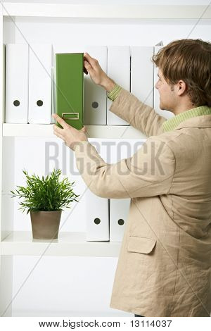 Businessman drawing out green folder in office.?