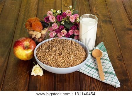 Bowl buckwheat cereal, a glass of milk, an apple, nuts and dried fruits, cotton napkin, spoon, a bouquet of roses on a background of dark wood.