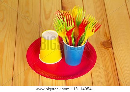 Colorful disposable tableware: glasses, plates and forks on a background of light wood.