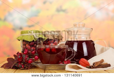 In glass jars of rowan berries, rose hips, a jug of drink, a cup of tea and cinnamon sticks on a background of autumn leaves.