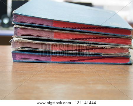 Blue and red business office document file on wooden table. Important business document report on desk.