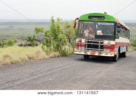 Masaya Nicaragua - July 24 2015: Old colorful chicken bus packed with people makes its way up the paved road to the craters of Masaya and Nindiri volcanoes on July 24 2015 in Masaya Nicaragua.