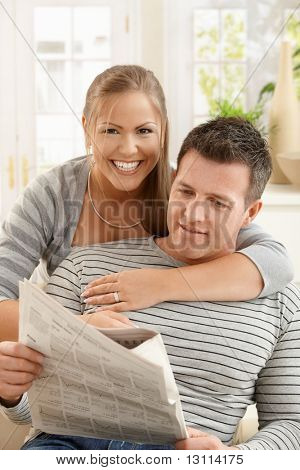 Smiling couple reading newspaper together in sitting room, hugging.?