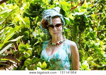 Beautiful brunette in a colored turban and a bathing suit in a tropical garden, Arusha, Tanzania