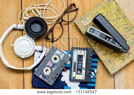Head Phone Cassette Tape Glasses Diary And Old  100 22Mm. Film Camera  Were Laying Down On Wooden Fl