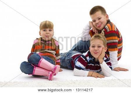 Gruppe von 3 glückliche Kinder auf farbenfrohe, trendige Kleidung, Boden liegend kleben ihre Toungues o
