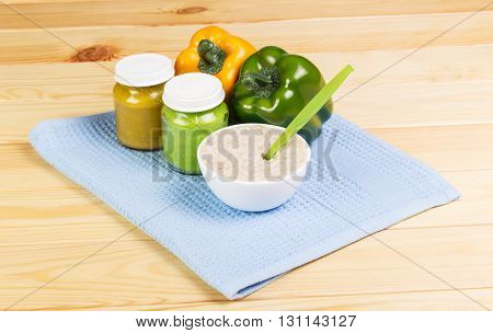 Food for children: a jar of vegetable sauce, a bowl of oatmeal, sweet pepper and cotton cloth on a background of light wood.
