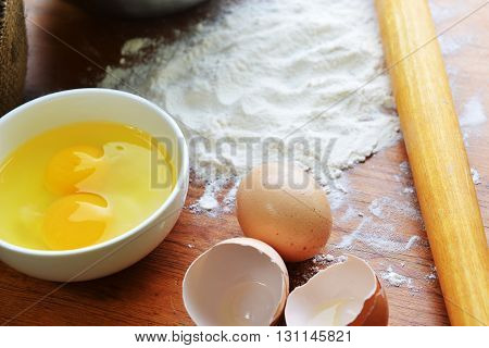 Kitchen rolling pin eggs and flour on wooden background