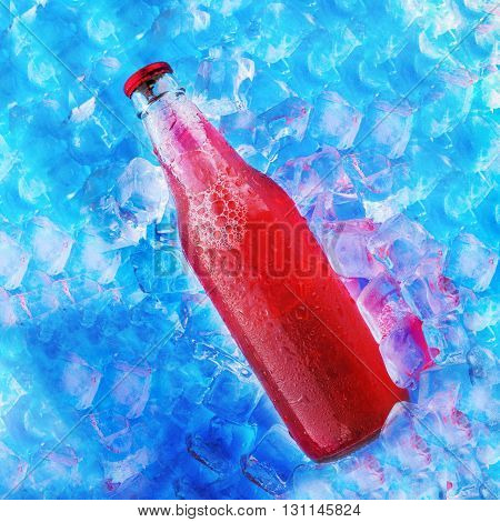 bottle with tasty red drink in ice