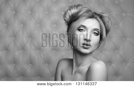 Studio portrait of a sexy blond, over leather upholstery background. Elegant luxury woman with a seductive neckline and bare shoulders looks into the camera.