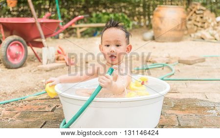 Top View Asian Baby Boy Outdoor Bathing In The White Bathtub . He Is Smiling And Playing Yellow Duck