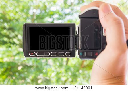 Hand Taking Blank Black Screen Video Camcorder  With Bokeh Green Tree Bush Nature Background