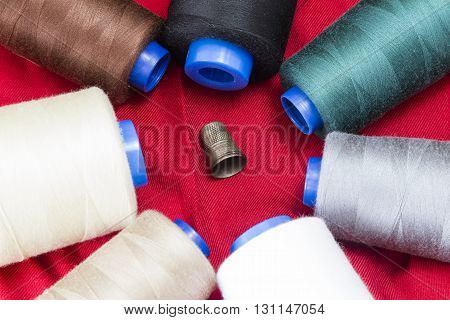 Several spools of thread of different colors and sizes with a thimble
