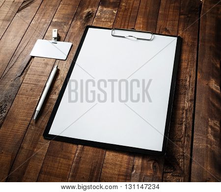 Blank paperwork template. Clipboard with blank white paper letterhead pen and badge on vintage wooden table background. Responsive design mock-up. Blank stationery set.