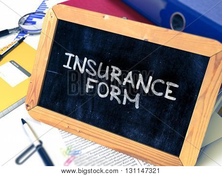 Insurance Form Handwritten on Chalkboard. Composition with Small Chalkboard on Background of Working Table with Ring Binders, Office Supplies, Reports. Blurred Background. Toned Image. 3D Render.