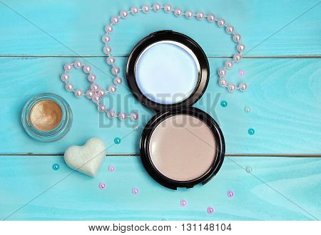 Facial powder, sparkling golden cream eyeshadow, white heart shaped soap and colorful pearl beads on painted blue wooden background