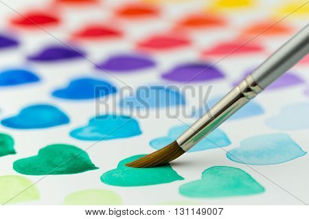 Multicolored hearts being painted with a watercolor paintbrush and paint. Narrow depth of field.