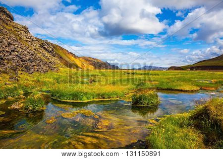 The picturesque valley in Landmannalaugar national park. Summer in Iceland. Green grass among hot springs