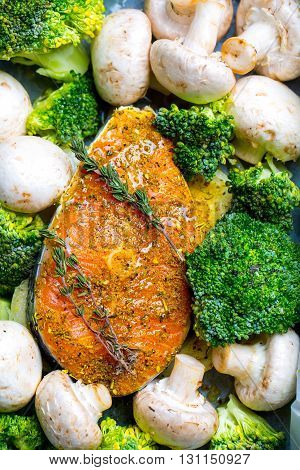 Salmon steak fresh raw fish with champignons broccoli spices and rosemary vegetables for cooking