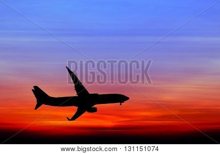 Silhouetted of commercial airplane flying at sunset