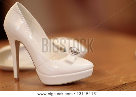 Pair of wedding bridal gorgeous fashion white shoes on high heel standing on wooden background