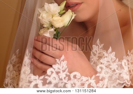Bridal hands holding beautiful wedding boutonniere of white roses flowers near her face covered with elegant marriage veil