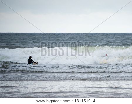 Wales UK - October 22 2015 : A surfer on a cold day looks on as her friend falls of her surf board.