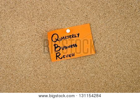 Qbr As Quarterly Business Review Written On Orange Paper Note