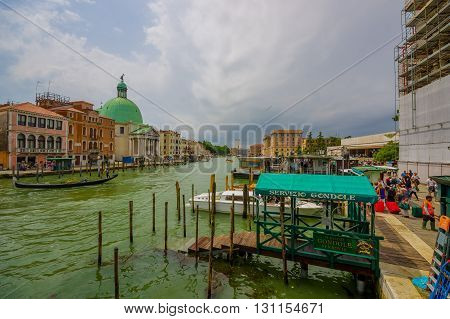VENICE, ITALY - JUNE 18, 2015: Goldola port for turists in Venetian canal, water runs all around the city. Green dome view.