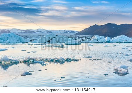 Beautiful view of icebergs in Jokulsarlon glacier lagoon at sunset Iceland; selective focus