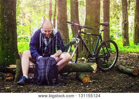 Cyclist stopped to rest and opened the backpack in beautiful forest summertime journey