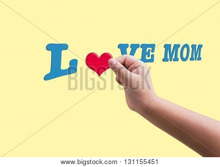 Isolated child or kid hand hold red heard form filling to blue text love mom on yellow plain background