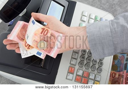 Hand Giving Change In Euro From The Till